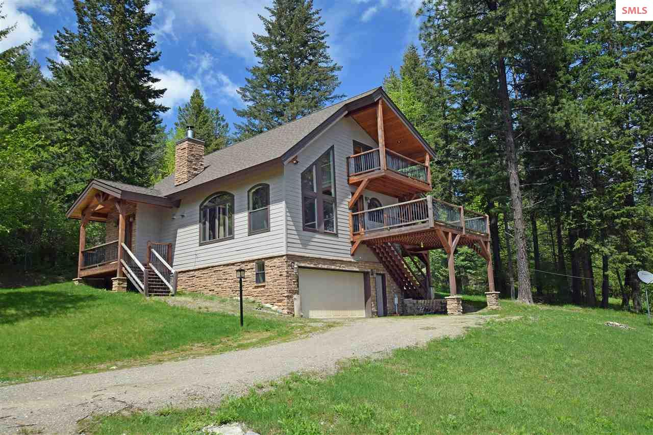 Come enjoy the serene atmosphere of this beautiful custom designed home tucked away in the woods with views of the lake! This 2,424 SF 3 BR, 2 BA home is situated on over 1½ acres! Quiet solitude abounds & nice custom features are ample in this amazing home. Amenities include knotty alder wood doors, custom ceramic tile, high efficiency heat pump, huge red cedar decks, & a gorgeous wood burning fireplace. The kitchen has many upgrades, & a quaint elevated dining area that overlooks the fireplace as you dine in style! The master features 2 walk-in closets, rain-glass shower & skylights, whirlpool, a double hickory vanity & granite counters. Enjoy your morning coffee right from your own private balcony off your master bedroom with views of the lake. Such a quiet location, come see today!