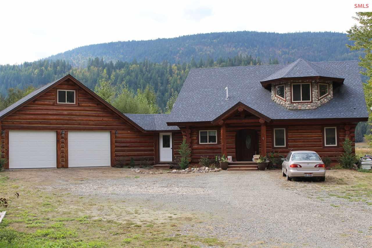 Gorgeous Caribou Log home with majestic views of the Selkirk Mts and 200' of Deep Creek frontage. Such a peaceful setting including a natural pond in front yard. Total of 3-4 bedrooms and four bathrooms in this cozy approx. 3,000 sq' on 3.32 acres.  Potentially two master bedrooms, one on the main floor & one on the second level with bay window turret. Every room has immense enclosed carpeted storage areas. Quiet nook or office area on second level.  Spacious, open kitchen with island and pantry. Wood fireplace in dining room and majestic rock gas fireplace in living room. Walk through enclosed breezeway to upstairs bonus room or bedroom (331 sq') with half bath all above attached garage.  Good Internet and home is wired for back-up generator. Enjoy the yard with fenced  orchard and 48' x 16' raised garden bed. Store tools in 20' shed. Plus a small pasture for your animals. Well at 50 gpm! Original 2006 cost to build was over $500K. Quality construction throughout! Close to both towns.
