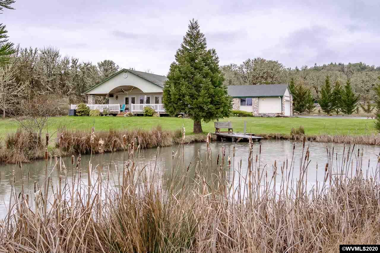 Accepted Offer with Contingencies. An Idyllic private country setting is perfect for this single level home located on 5 acres overlooking a large pond, meadows and forest. Spacious open floor plan with large wrap-around deck provides entertaining options both inside and out. Private master suite with private deck. Attached double car garage w/studio. A separate shop w/heated workspace, stocked pond and Office/Studio. Located within minutes of both Corvallis and Philomath. Opportunity is knocking with this rare property.