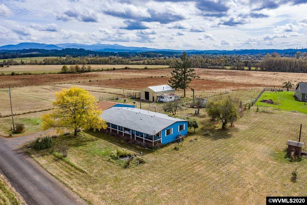 BRING YOUR HORSES! Here is your chance to own 7 acres of flat pasture in a beautiful country setting! This solid home is located on a dead end road, with a large shop, oversized door & horse stalls. Relax on your covered deck overlooking, the fish pond, garden beds & breathtaking views! So much more to this home including the gazebo, chicken coop, Goat house, shed, room for RV parking, etc! Don't wait on this buy!